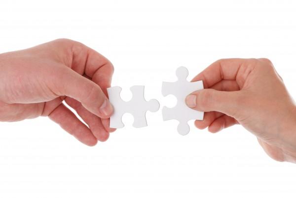 Two hands putting together a jigsaw puzzle isolated on white background